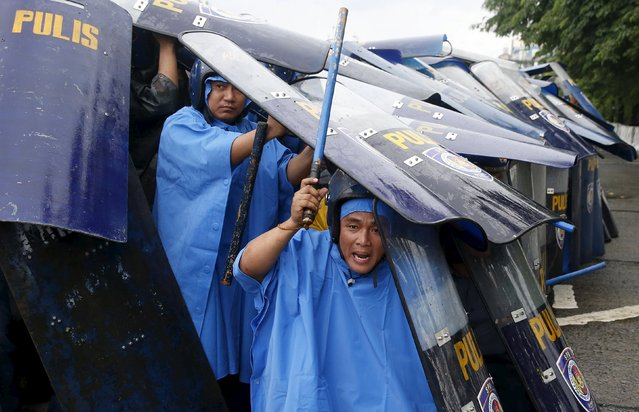 Policemen seek cover with their shields as they block protesters trying to march towards Batasang Pambansa, where Philippines President Benigno Aquino will address the joint session of Congress and deliver his last State of the Nation address in Quezon city, Metro Manila, Philippines July 27, 2015. (Photo by Erik De Castro/Reuters)