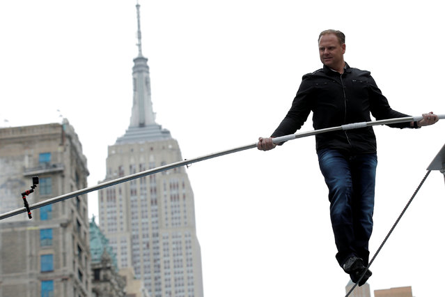 Aerialist Nik Wallenda walks a tightrope during a promotional event in midtown Manhattan, with the Empire State Building behind him, in New York City, U.S., May 17, 2016. (Photo by Brendan McDermid/Reuters)
