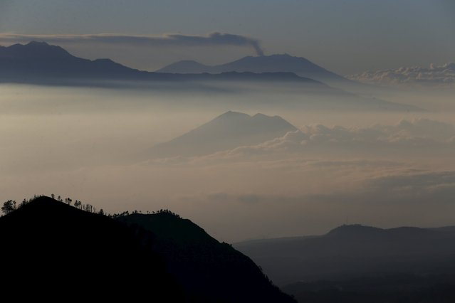 Mount Raung (top), in East Java, is seen spewing ash into the air from Mount Bromo in Indonesia's East Java province, July 31, 2015. (Photo by Reuters/Beawiharta)