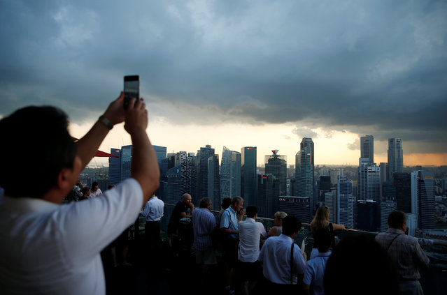 A man takes photos of storm clouds gathering over the skyline of Singapore's central business district June 6, 2016. (Photo by Edgar Su/Reuters)