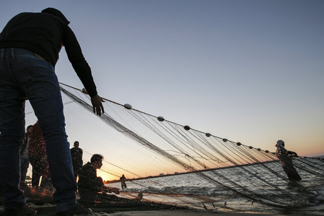 Palestinian fishermen retrieve their fishing nets back from the Mediterranean sea water at sunset in Gaza City on December 23, 2019. (Photo by Mohammed Abed/AFP Photo)