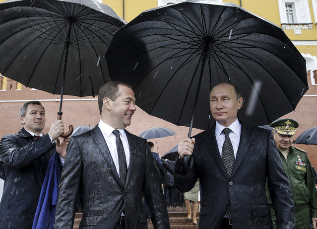 Russian Prime Minister Dmitry Medvedev, foreground left, and Russian President Vladimir Putin, foreground right, stand under umbrellas as thet take part in a wreath laying ceremony to the Tomb of Unknown Soldier in Moscow, Russia, on Thursday, June 22, 2017, marking the 76th anniversary of the Nazi invasion of the Soviet Union. (Photo by Alexei Druzhinin/Sputnik/Kremlin Pool Photo via AP Photo)