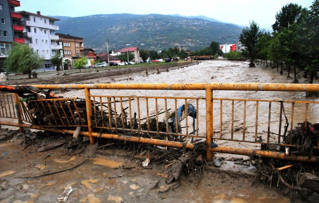 In this picture taken Monday evening, August 3, 2015, debris and mud are piled on a bridge over the Pena River during a flood in the town of Tetovo, northwestern Macedonia. (Photo by Zoran Andonov/AP Photo)