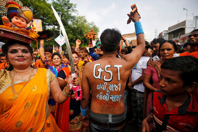 """A Hindu devotee shows his painted back with a message stating """"GST (Global Service Tax) – A new boon or a lasting burden?"""" ahead of the rollout of the new tax in India, during the annual Rath Yatra, or chariot procession, in Ahmedabad, June 25, 2017. (Photo by Amit Dave/Reuters)"""