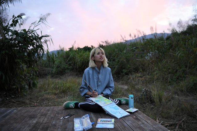 Chen Yan looks up as she paints on a hill during sunset at AnotherCommunity in Guanzhong village, Fuzhou, Fujian province, China on November 3, 2019. The small community preaches sustainable living and mindful consumption. China's teeming megacities have drawn hundreds of millions of people from rural villages and small towns in search of jobs and wealth, but people like Chen are part of an emerging trend in the opposite direction. (Photo by Tingshu Wang/Reuters)