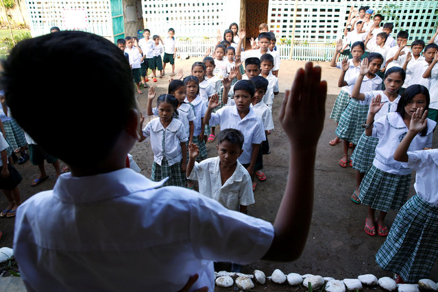 """Pupils recite """"Panatang Makabayan"""", an oath of allegiance to the country, during the opening of classes at a remote Casili Elementary School in Montalban, Rizal northeast of Manila, Philippines June 13, 2016. (Photo by Erik De Castro/Reuters)"""