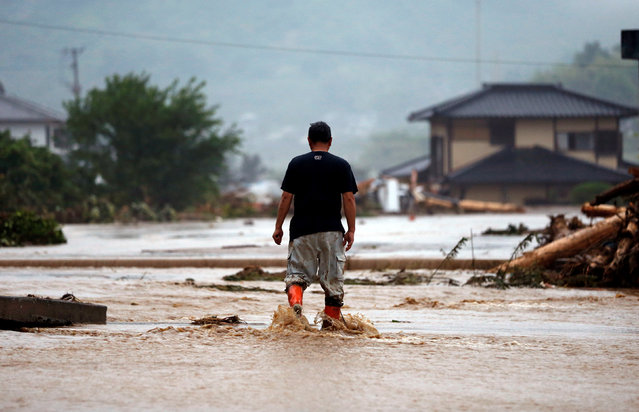 A local resident walks in an area damaged by swollen river after heavy rain in Asakura, Fukuoka Prefecture, Japan July 6, 2017. (Photo by Issei Kato/Reuters)