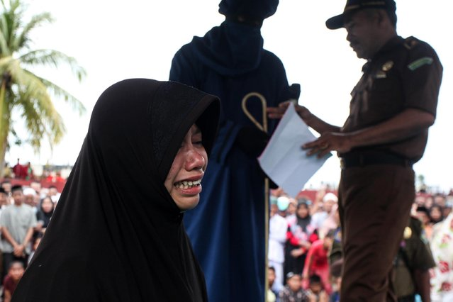 An Acehnese women is whipped in front of the public for violating sharia law in Pidie District on 14 July 2017, Aceh, Indonesia. (Photo by Oviyandi/Barcroft Images)