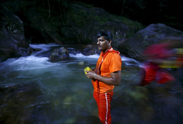 """A Hindu devotee offers a prayer as he stands on the Bagmati River during the """"Bol Bom"""" pilgrimage in Kathmandu August 10, 2015. (Photo by Navesh Chitrakar/Reuters)"""