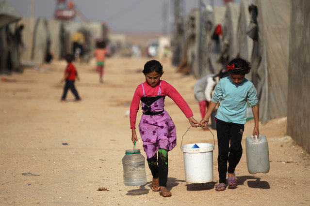 Internally displaced Syrian girls carry water containers in Jrzinaz camp, in the southern part of Idlib, Syria, June 21, 2016. (Photo by Khalil Ashawi/Reuters)