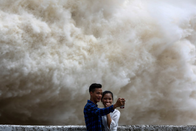A couple takes a selfie as Hoa Binh hydroelectric power plant opens the flood gates after a heavy rainfall caused by Talas typhoon in Hoa Binh province, outside Hanoi, Vietnam July 20, 2017. (Photo by Reuters/Kham)