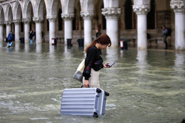 A tourist carries her luggage in a flooded St. Mark's Square, in Venice, Wednesday, November 13, 2019. The high-water mark hit 187 centimeters (74 inches) late Tuesday, Nov. 12, 2019, meaning more than 85% of the city was flooded. The highest level ever recorded was 194 centimeters (76 inches) during infamous flooding in 1966. (Photo by Luca Bruno/AP Photo)