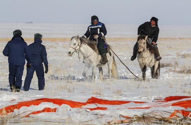 Kazakh shepherds ride near a parachute close to the place where Russian Soyuz MS-13 space capsule landed about 150 km (90 miles) south-east of the Kazakh town of Zhezkazgan, Kazakhstan, Thursday, February 6, 2020. (Photo by Sergei Ilnitsky/Pool Photo via AP Photo)