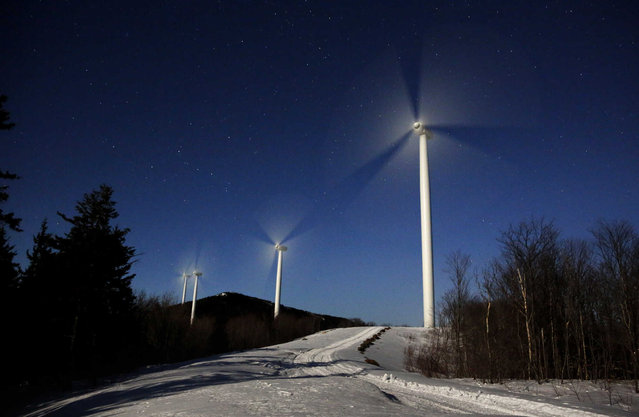 The blades of wind turbines spin under the light of a full moon at the Saddleback Ridge Wind Project, early Wednesday morning, March 20, 2019, in Carthage, Maine. The first day off spring blew in with gentle winds and cold temperatures. Warmer and wetter weather is expected later in the week. (Photo by Robert F. Bukaty/AP Photo)
