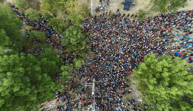 An aerial view taken from a drone of migrants queueing to pass the Greek-FYROM border to Gevgelija, The Former Yugoslav Republic of Macedonia, from the border village of Idomeni, northern Greece, 21 August 2015. Macedonian police clashed with thousands of migrants attempting to break into the country after being stranded in no-man's land overnight, marking an escalation of the European refugee crisis for the Balkan country. (Photo by Nikos Arvanitidis/EPA)