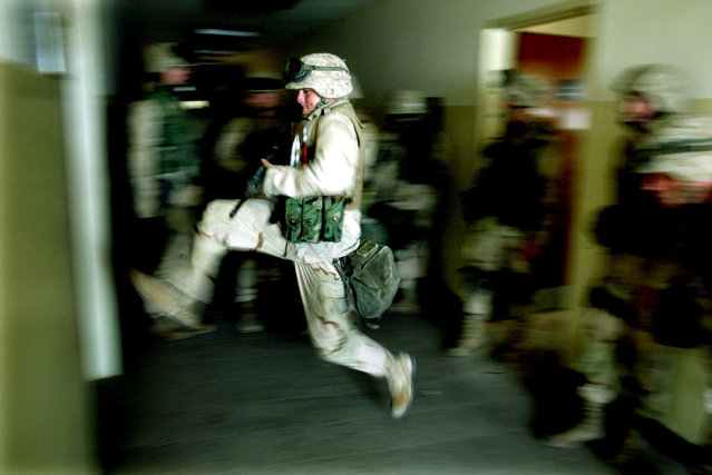 U.S. Marines kick in a door while securing a building next to the main hospital in central Baghdad April 15, 2003, which will be used as a temporary Iraqi police headquarters. (Photo by Jerry Lampen/Reuters)