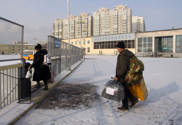 Chinese citizens passing through a temporary corridor opened at a border checkpoint between Blagoveshchensk and Heihe in Blagoveshchensk, Russia on February 1, 2020. Temporary corridors are opened to return Russian and Chinese citizens to their countries as the Russian government orders to close the border with China as a measure to prevent the coronavirus spread. All the people passing through the temporary corridor are tested for the virus. The 2019-nCoV pneumonia-like coronavirus outbreak began in Wuhan, China, in late December 2019; according to the latest reports, about 11,000 people globally have been infected, 259 have died from the virus. (Photo by Svetlana Mayorova/TASS)