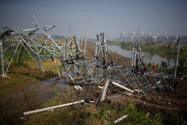 A rescue worker works on a damaged high-voltage tower after a tornado hit Funing on Thursday, in Yancheng, Jiangsu province, June 25, 2016. (Photo by Aly Song/Reuters)