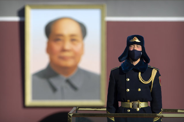 In this Tuesday, February 4, 2020 file photo, a member of an honor guard wears a face mask as he stands guard in Tiananmen Square in Beijing. On Wednesday, March 17, 2020, China announced that it will revoke the media credentials of American journalists at three major U.S. news organizations, in effect expelling them from the country, in response to new U.S. restrictions on Chinese state-controlled media. (Photo by Mark Schiefelbein/AP Photo)