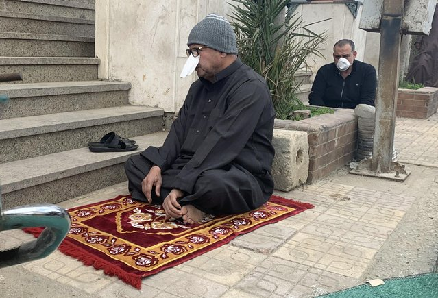 Professor Reda Abd El Wahed, a 65-year-old, draping a white handkerchief over his nose as an extra precaution against coronavirus, attends Friday prayers outside Abdel Rahman Mosque in the Cairo neighborhood Maadi, Egypt, March 20, 2020. The coronavirus stopped communal Muslim prayers for the first time in living memory in many mosques from Indonesia to Morocco on Friday. (Photo by Amr Abdallah Dalsh/Reuters)