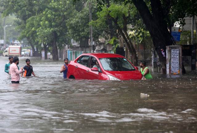 People help a woman to move her car through a water-logged road during rains in Mumbai, August 29, 2017. (Photo by Shailesh Andrade/Reuters)