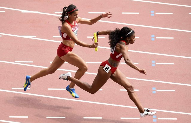 Jasmine Todd of the U.S. (R)  receives the baton from teammate Jenna Prandini as her team competes in the women's 4 x 100 metres relay heat during the 15th IAAF World Championships at the National Stadium in Beijing, China August 29, 2015. (Photo by Dylan Martinez/Reuters)