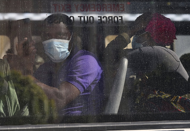 Foreign migrants wait on a bus after police removed them from the Central Methodist Church in Cape Town, Sourth Africa, Thursday, April 2, 2020. The migrants, who had been sheltering there for months, refused to leave the church and had previously demanded that South Africa relocate them to other countries, including the United States and Canada, because they had been victims of xenophobic threats in South Africa last year. (Photo by AP Photo/Stringer)