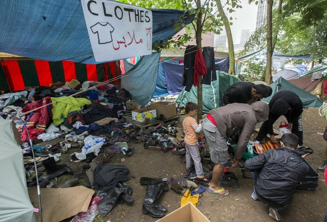 Asylum seekers search for clothes in a makeshift camp outside the foreign office in Brussels, Belgium September 3, 2015. Europe has seen a huge influx of migrants from the Middle East and Africa trying to escape poverty and violence at home and the issue has shot to international prominence as thousands try to make their way to Britain from the French port of Calais. Some 2,300 people requested asylum in Belgium in June alone, up by a third from May, official figures show. (Photo by Yves Herman/Reuters)