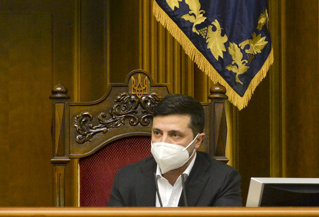 Ukrainian President Volodymyr Zelenskiy wearing a face mask to protect against coronavirus speaks during an extraordinary parliamentary session in Kyiv, Ukraine, Monday, March 30, 2020. Ukraine has been under quarantine since March 12. (Photo by AP Photo/Stringer)