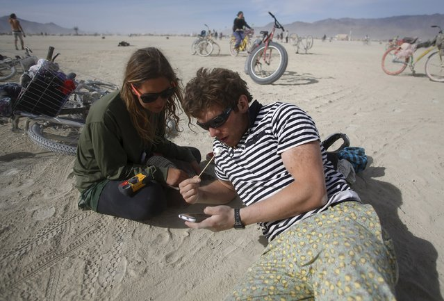 """Natalie Campos (L) and Henry Waite look at photos while resting on the Playa during the Burning Man 2015 """"Carnival of Mirrors"""" arts and music festival in the Black Rock Desert of Nevada September 5, 2015. (Photo by Jim Urquhart/Reuters)"""