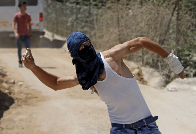 A masked Palestinian throws stones during a protest against what organizers say is land confiscation by Israel to make way for the Israeli barrier in the occupied West Bank city of Beit Jala, near Bethlehem September 6, 2015. (Photo by Mussa Qawasma/Reuters)