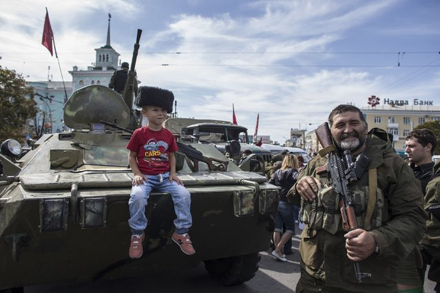 A boy sits on an armored personnel carrier (APC) as he poses for a picture during a parade in Luhanks, eastern Ukraine, September 14, 2014. (Photo by Marko Djurica/Reuters)