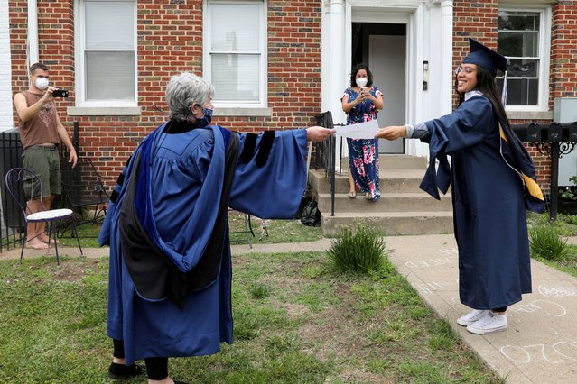 George Washington University graduate Catalina Perez (R) receives a paper copy of her diploma from neighbor Paula Lytle as they keep a social distance at a surprise graduation party for Perez, who completed her undergraduate studies in International Affairs across the span of ten years only to miss her commencement due to the coronavirus disease (COVID-19) outbreak in Washington, U.S., May 17, 2020. (Photo by Jonathan Ernst/Reuters)
