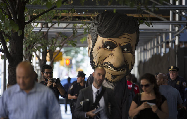 A giant caricature of Iranian President Mahmoud Ahmadinejad goes up Sixth Avenue near the Warwick hotel during a protest against the controversial leader in New York, on September 24, 2012. The mid-town Manhattan hotel is housing Iranian president Mahmoud Ahmadinejad as the 67th United Nations General Assembly is held nearby. (Photo by John Minchillo/Associated Press)