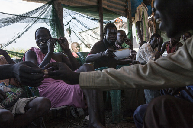 Men drink locally made beer called Acelea at a bar in the Protection of Civilians (POC) site at the United Nations Mission in South Sudan (UNMISS) compound in Malakal, South Sudan on Saturday, July 9, 2016. Alcohol is prohibited in the site as it causes too much violence between the men. The Malakal POC site houses over 32,000 displaced people mainly from the Shilluk and Nuer tribes. In February of this year, members of the Dinka tribe, who resided in the camp at the time, carried out a coordinated attack within the site leading to the destruction of hundreds of shelters and many deaths. Since then, most members of the Dinka tribe have fled to Malakal town where they occupy the homes of those still displaced. (Photo by Jane Hahn/The Washington Post)