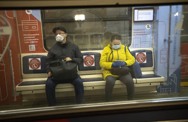People wearing face masks and gloves to protect against coronavirus, observe social distancing guidelines as they ride a carriage in the subway on the escalator in Moscow, Russia, Wednesday, May 13, 2020. Wearing face masks and latex gloves is mandatory for people using Moscow's public transport. President Vladimir Putin declared an end to a partial economic shutdown across Russia due to the coronavirus pandemic, but he said that many restrictions will remain in place. (Photo by Alexander Zemlianichenko/AP Photo)