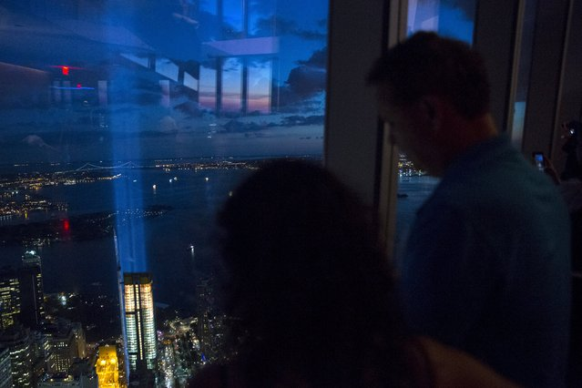 People peer through the windows at One World Observatory, the observation deck at One World Trade Center, as the Tribute in Light installation shines in Lower Manhattan in New York September 11, 2015. (Photo by Andrew Kelly/Reuters)