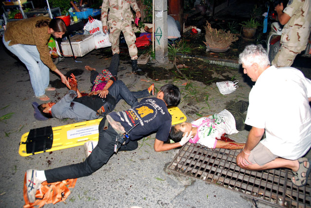 In this Thursday, August 11, 2016, photo, the injured are helped after a bomb blast in the southern resort city of Hua Hin, 240 kilometers (150 miles) south of Bangkok, Thailand. Police are investigating a series of bomb blasts in Hua Hin and other cities in Thailand. (Photo by Daily News via AP Photo)