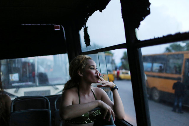 A reveller smokes a cigarette before performing at a carnival parade in Havana, Cuba, August 12, 2016. (Photo by Alexandre Meneghini/Reuters)