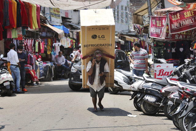 An Indian laborer talks on his mobile phone as he transports a refrigerator on his back at a market in Jammu, India, Sunday, June 7, 2020. India whose coronavirus caseload is fifth highest in the world has partially restored trains and domestic flights and allowed reopening of shops and manufacturing. (Photo by Channi Anand/AP Photo)