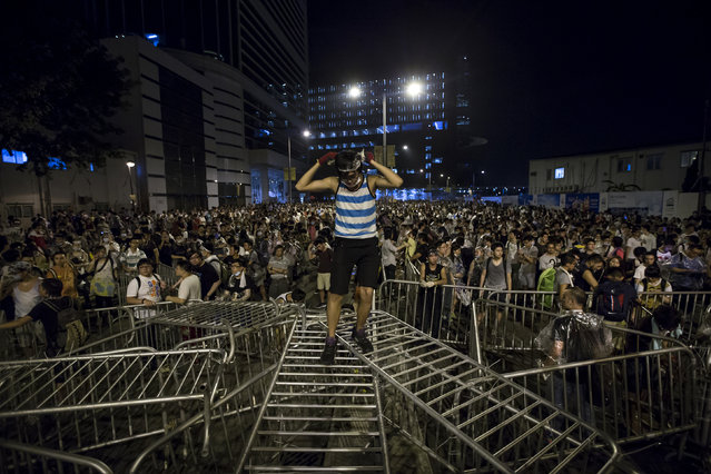 A pro-democracy student stands on railings during a rally outside the government headquarters in Hong Kong, as riot police stand guard, early September 28, 2014. (Photo by Tyrone Siu/Reuters)