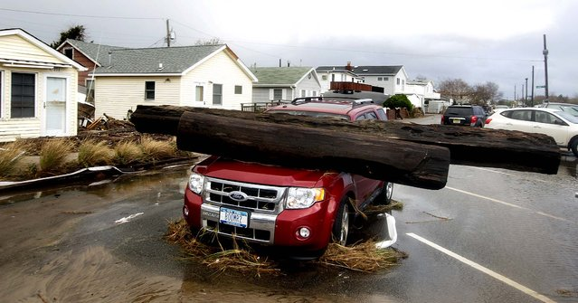A log rests on a vehicle damaged by superstorm Sandy at Breezy Point. (Photo by Frank Franklin II/Associated Press)