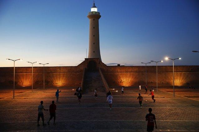 Boys play football in front of a lighthouse near Rabat's Medina September 23, 2014. (Photo by Damir Sagolj/Reuters)