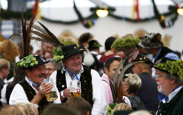 Men in traditional Bavarian attire cheer with beer during the 182nd Oktoberfest in Munich, Germany, September 19, 2015. (Photo by Michaela Rehle/Reuters)