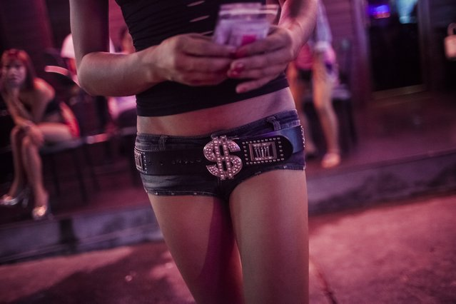 A ladyboy s*x worker wears a belt with a dollar sign on it while holding condoms and lube handed to her by Sisters, a transgendered outreach and community services organization in Pattaya, Thailand on August 25, 2016. Many of Thailand's ladyboys live in Pattaya, a large percentage of whom work in the s*x industry there. (Photo by Aaron Joel Santos/Getty Images/Aurora Creative)