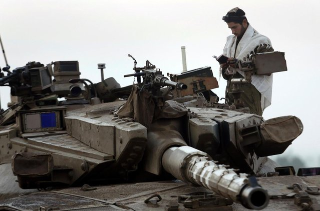 An Israeli soldier prays atop a tank at a staging area near the border with central Gaza November 20, 2012. (Photo by Yannis Behrakis/Reuters)