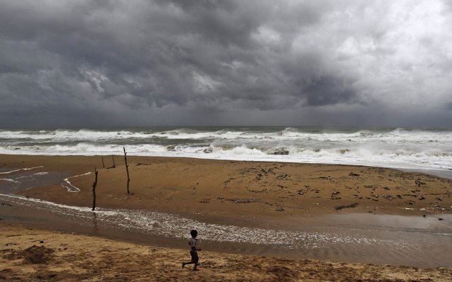 "An Indian boy plays on the beach as waves break on the Bay of Bengal coast near Gopalpur, in Ganjam district, 140 kilometers (87 miles) south of Bhubaneswar, India, Saturday, October 11, 2014. The India Meteorological Department described Cyclone Hudhud as a ""very severe"" storm that could pack winds of 195 kilometers (120 miles) per hour and cause torrential rains when it makes landfall near the port city of Visakhapatnam around noon Sunday. (Photo by Biswaranjan Rout/AP Photo)"