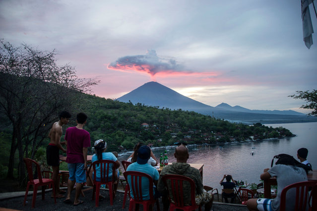 Tourists gather to watch Mount Agung at Amed beach in Karangasem on Indonesia' s resort island of Bali on November 30, 2017. Thousands of foreign tourists were expected to leave Bali by plane on November 30 following a nearly three- day airport shutdown sparked by a rumbling volcano on the Indonesian holiday island. (Photo by Juni Kriswanto/AFP Photo)