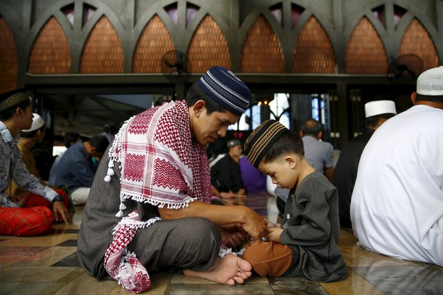 A boy plays with his father while Muslim men gather to pray in a mosque during the festival of Eid-al-Adha in Bangkok, Thailand, September 24, 2015. (Photo by Jorge Silva/Reuters)