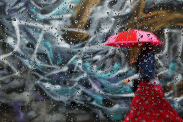 A woman walks past graffiti on a wall in the Williamsburg neighborhood of the borough of Brooklyn, in New York, September 16, 2014. The picture was taken through car window with raindrops. (Photo by Shannon Stapleton/Reuters)